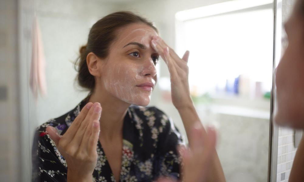 Woman washing face in mirror