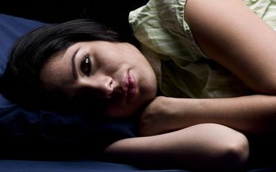 Hispanic young woman laying in bed sleepless on black background