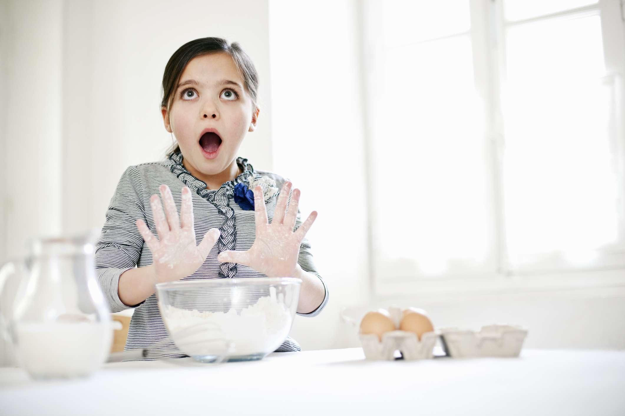 Girl standing at counter with baking ingredients