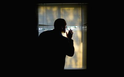 A man peeking outdoors through the blinds of a darkened room