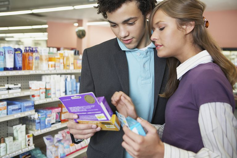 young couple looking at condoms in store