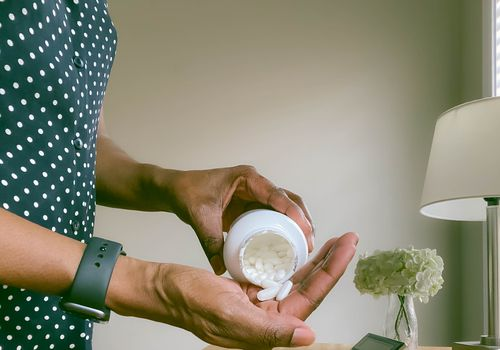A Black person pouring a couple of pills into their hand.