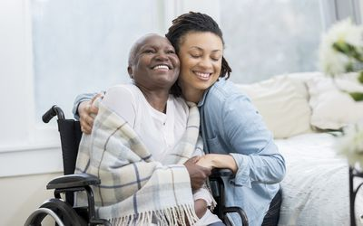 Woman embraces her wheelchair-bound mother