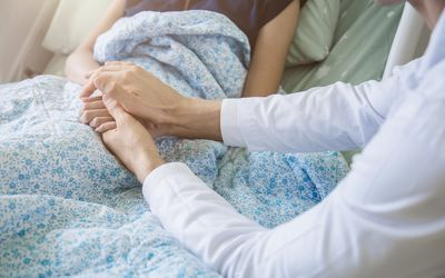 Doctor holding patient's hand, helping hand concept and comforting her