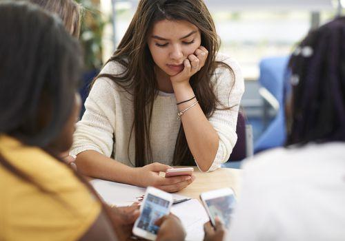 Teen girl scrolling on phone in class.