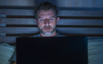 Man with laptop computer in bed