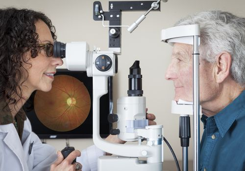 Doctor performing eye exam on elderly man