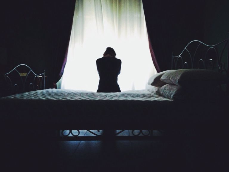 Woman sitting on the edge of a bed in a dark room