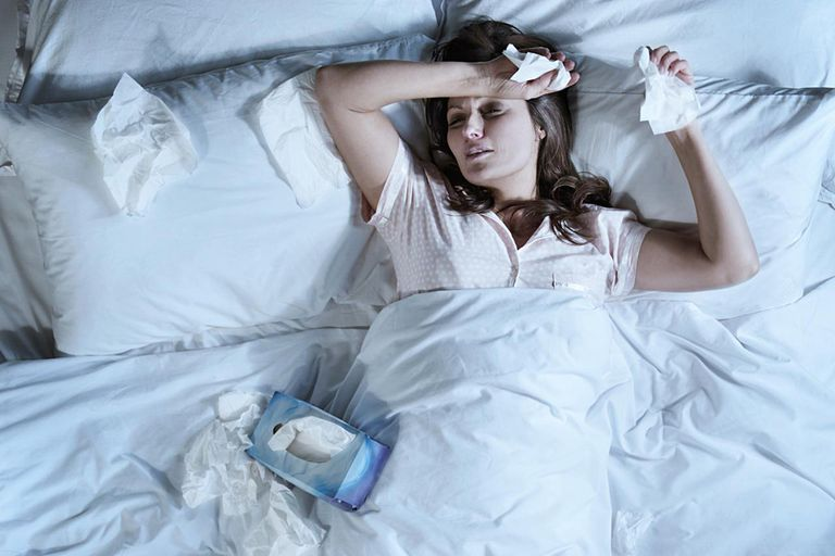 Woman with a cold lying in bed holding tissues