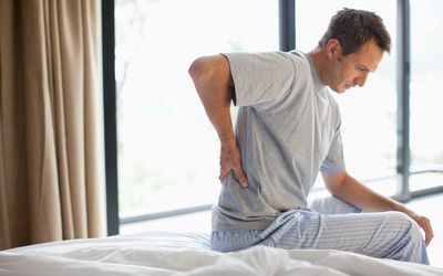 Man sitting on bed with backache