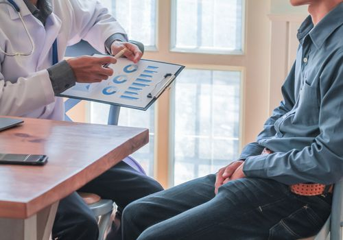 man sitting with doctor looking at charts
