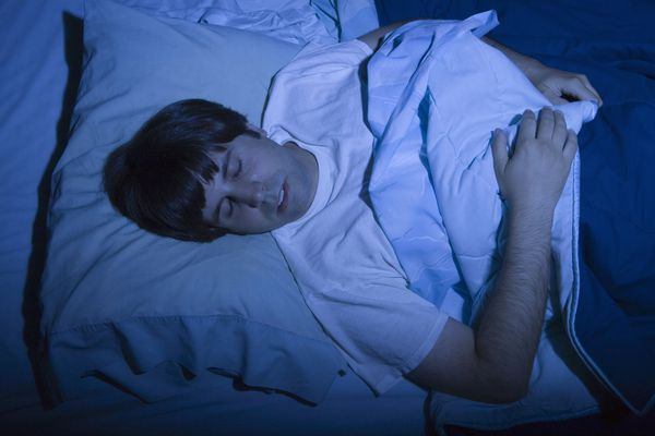man in dark room sleeping may be at risk for parasomnia called sexsomnia