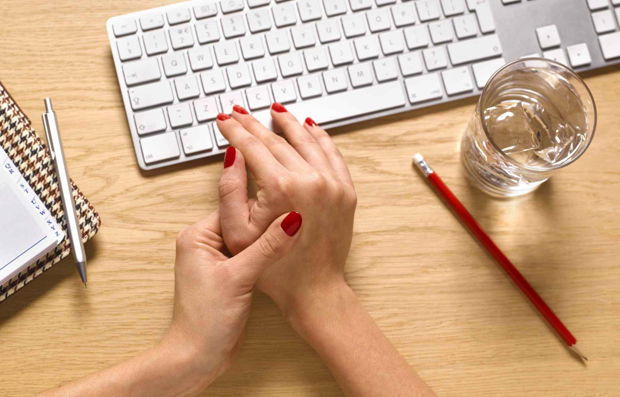 A woman is using her left hand to rub her right hand between the thumb and index finger. Next to her hands is a glass of water, a pencil, and keyboard.