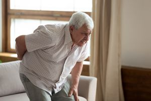 Senior man got up from couch felt low back pain