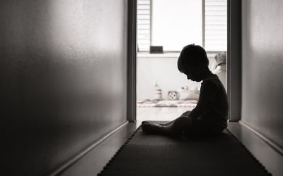 A young child in shadow sitting alone in a hallway.