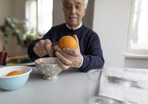 Man cutting an orange