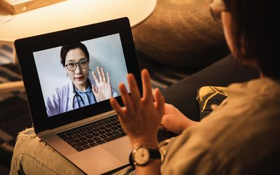 consulting asian doctor online using laptop