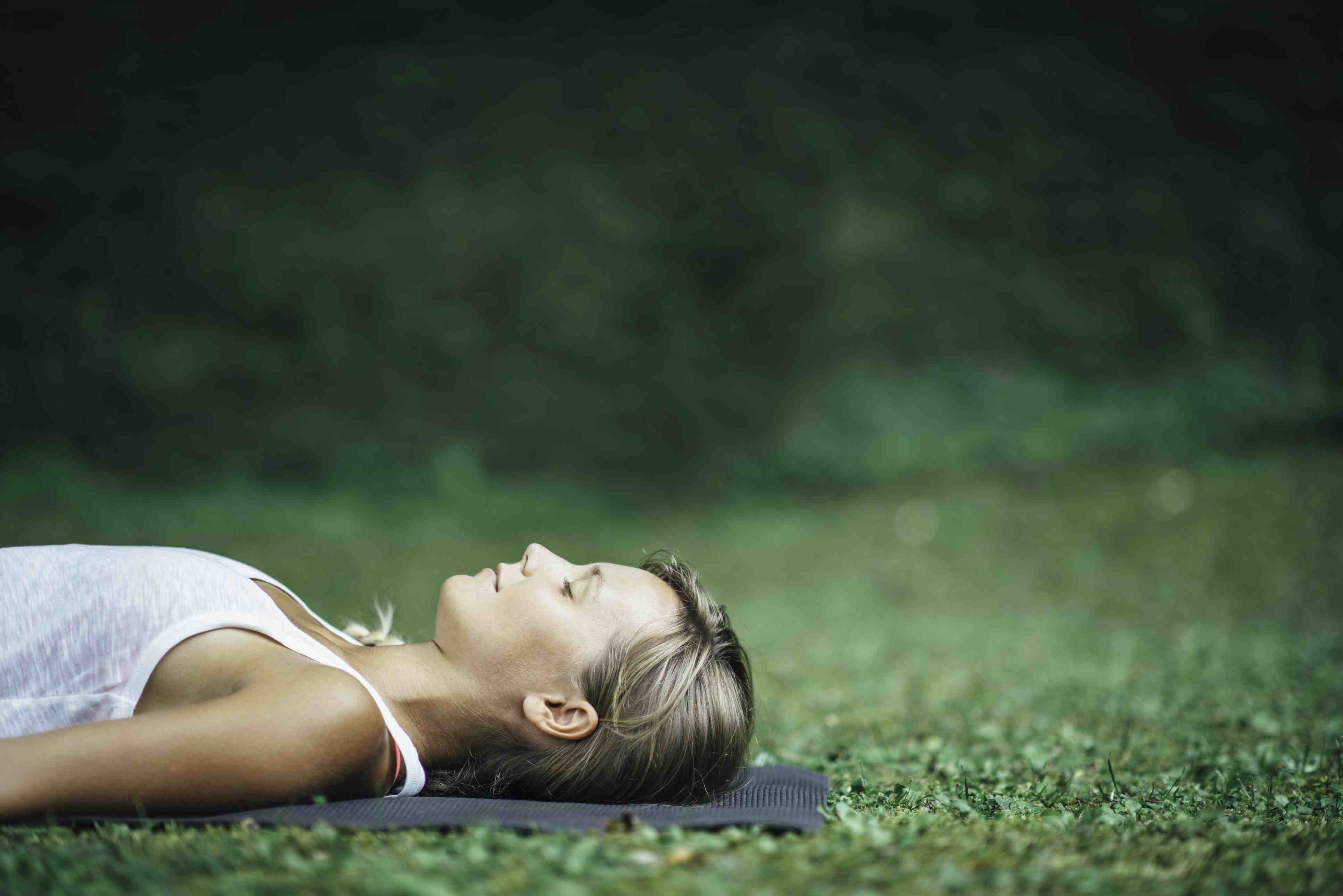 A woman relaxing on a yoga mat