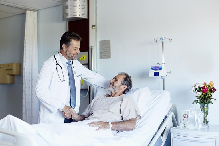Doctor greeting patient in hospital ward