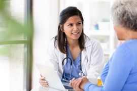 Female patient listens carefully to mid adult female doctor