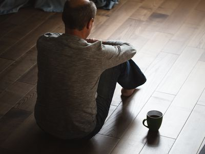man sitting on floor distraught
