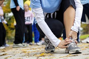 Woman holding her hurt ankle at a race.