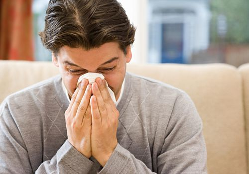Adult on couch blowing his nose