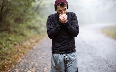 Young man warming his hands during cold in nature