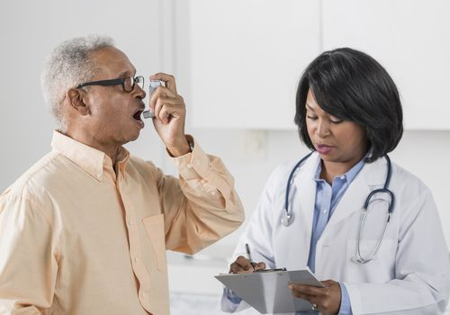 African American doctor with man using asthma inhaler - stock photo