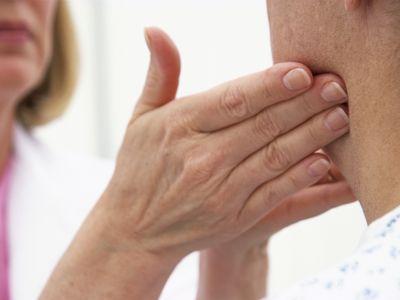 Female doctor feeling a male patient's lymph nodes