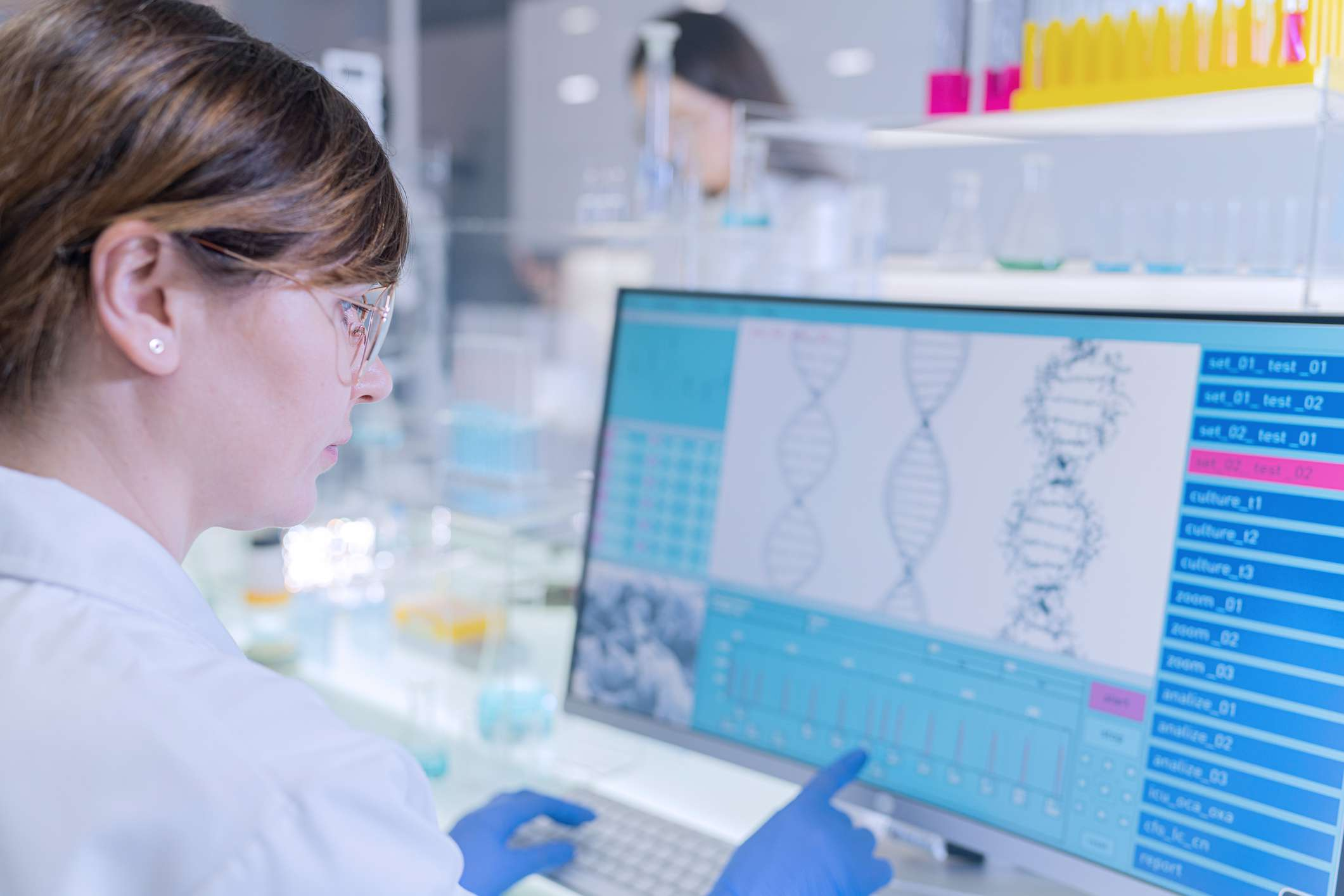 Female research team studying DNA samples. Computer screens with DNA helix in foreground