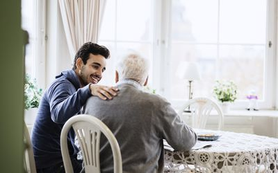 Young man acting as a caregiver for an older man.