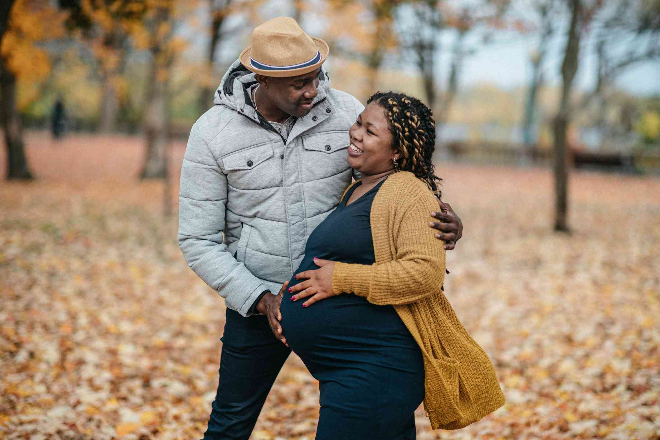 A couple enjoys a walk in the park during pregnancy