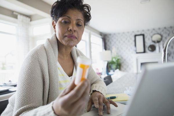 Woman looking at prescription pill bottle