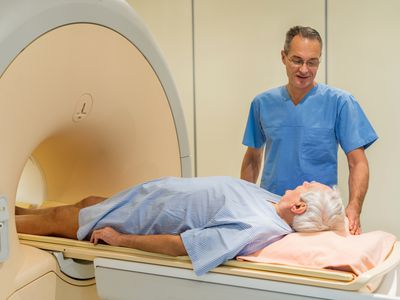 Radiologist talking to a senior patient at MRI scan. - stock photo