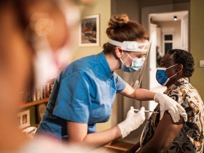 A white nurse administering a vaccine to a black man.