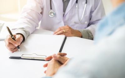 Midsection Of Doctor Discussing With Patient At Table In Clinic