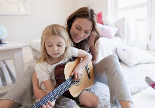 A mother and daughter playing guitar together