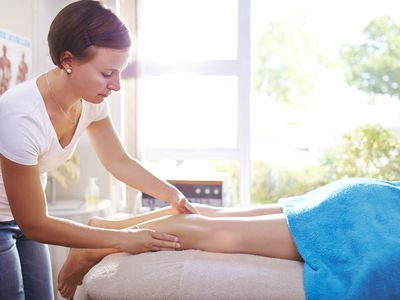 Massage therapist working on patient's legs