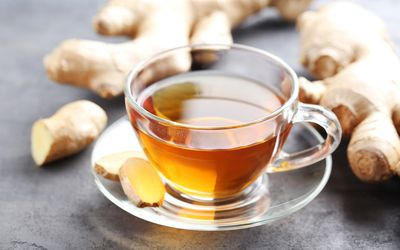 Cup of tea with ginger root on grey wooden table