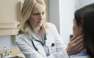 Female doctor checking patient's neck