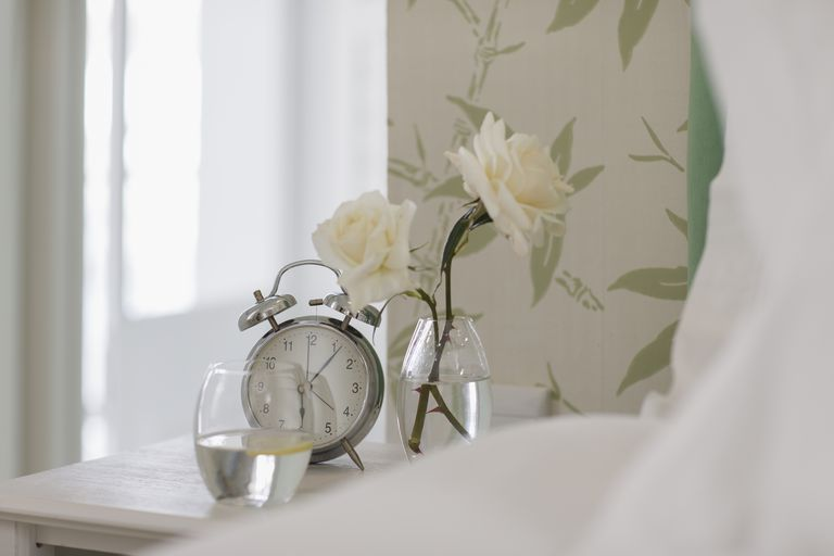 6bd64e6ba6d2c White roses, alarm clock and water glass on bedside table
