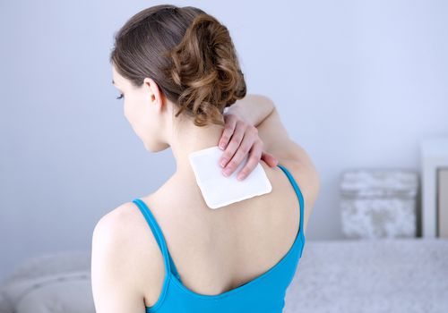 Woman applying pain patch.