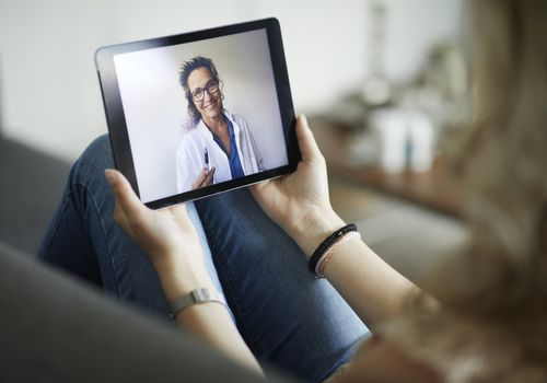 Women holding tablet during telemedicine visit with provider