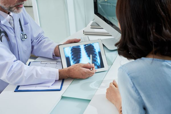 doctor pointing to chest X-ray explaining to a female patient why her stage 3 lung cancer is unresectable (inoperable)