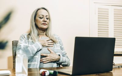 Senior woman doing breathing exercise during online consultation at home