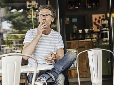 Man sitting outside cafe smoking a cigarette