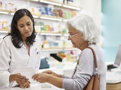 Senior customer showing prescription to female doctor. Cashier is assisting elderly woman at checkout counter. They are standing at pharmacy.