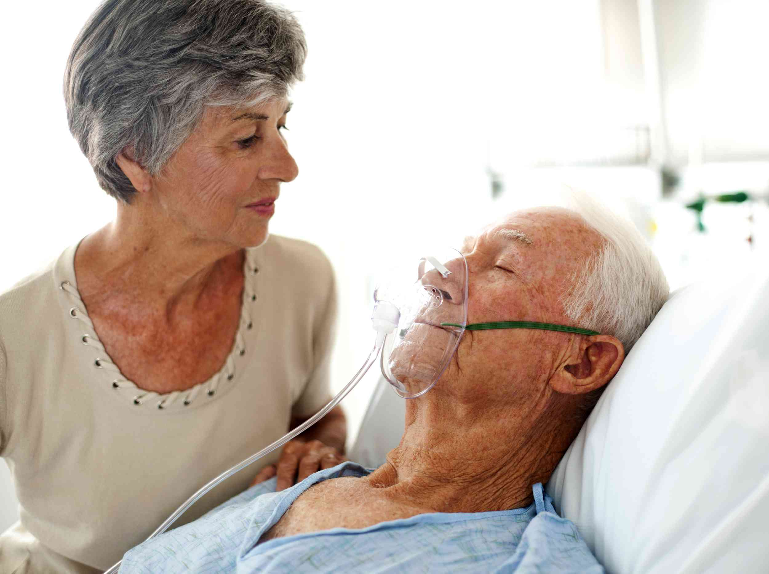 Woman looking at man wearing oxygen mask
