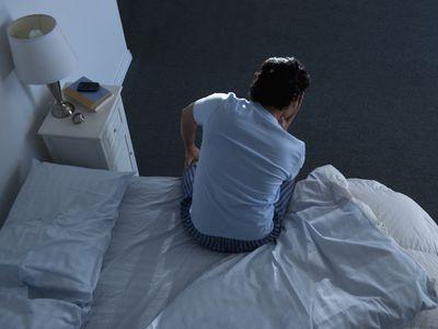 Man awake sitting up on edge of bed at night